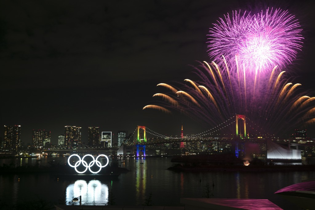 Fireworks light up the sky near the illuminated Olympic rings during a ceremony held to celebrate the 6-months-to-go milestone for the Tokyo 2020 Olym...