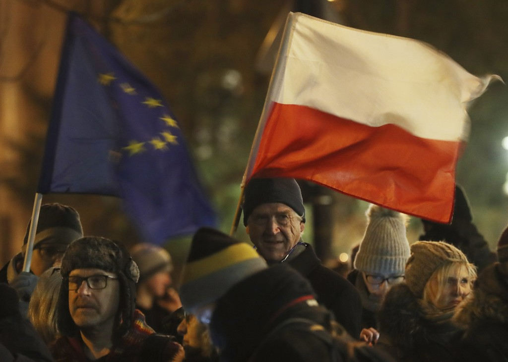 People holding a Poland and European Union flags take part in a protest outside Poland's parliament building as lawmakers voted to approve the much-cr...