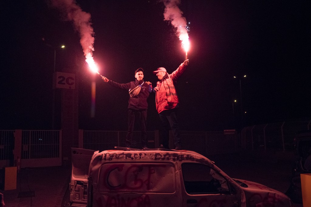 Demonstrators stand on top of a vandalized car with flares during a blockade of the Marseille port in southern France, Thursday, Jan. 23, 2020. Protes...