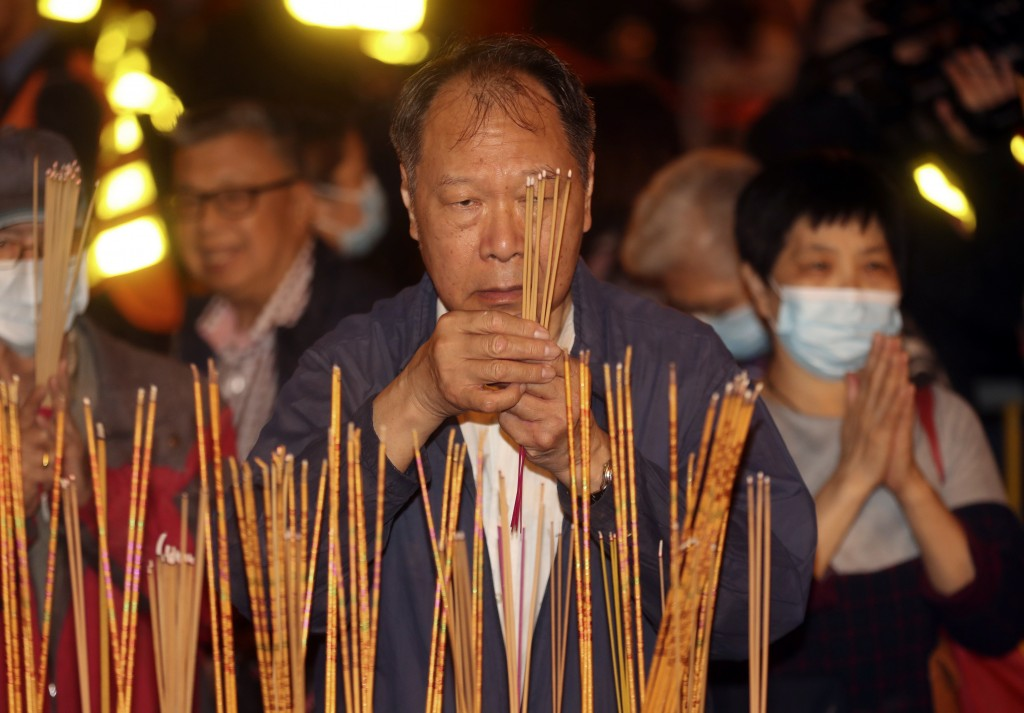 A man burn joss sticks as he prays at the Wong Tai Sin Temple, Friday, Jan. 24, 2020, in Hong Kong, to celebrate the Lunar New Year which marks the Ye...