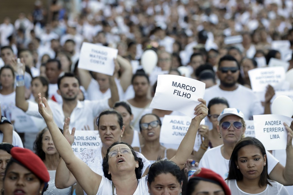 FILE - In this Feb. 1, 2019 file photo, friends and relatives hold signs with the names of victims, during a march paying homage to the victims of a m...