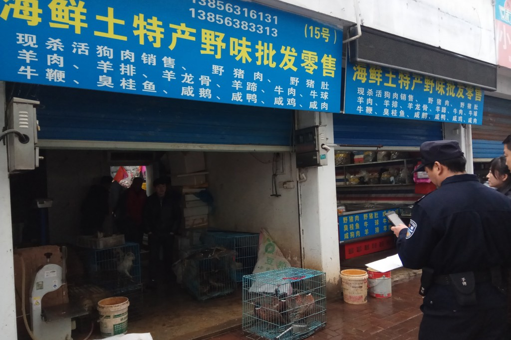 In this Jan. 9, 2020, photo provided by the Anti-Poaching Special Squad, police gather outside a store suspected of trafficking wildlife in Guangde ci...