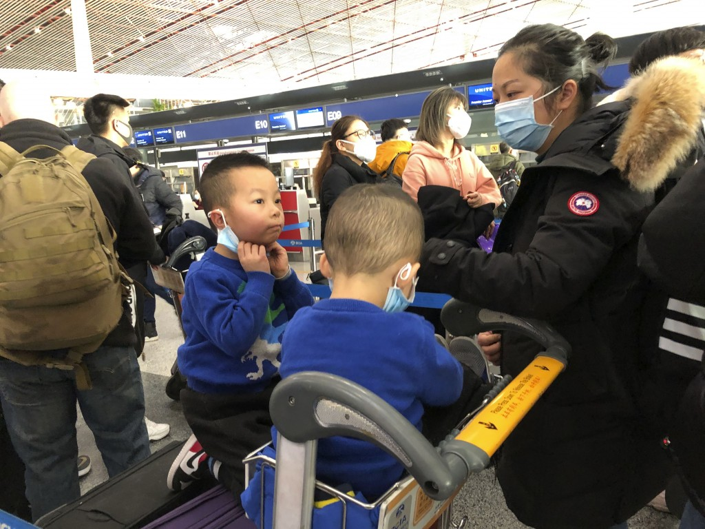 FILE - In this Saturday, Jan. 25, 2020, file photo, children adjust their face masks as they wait in line at check-in counters at Beijing Capital Inte...