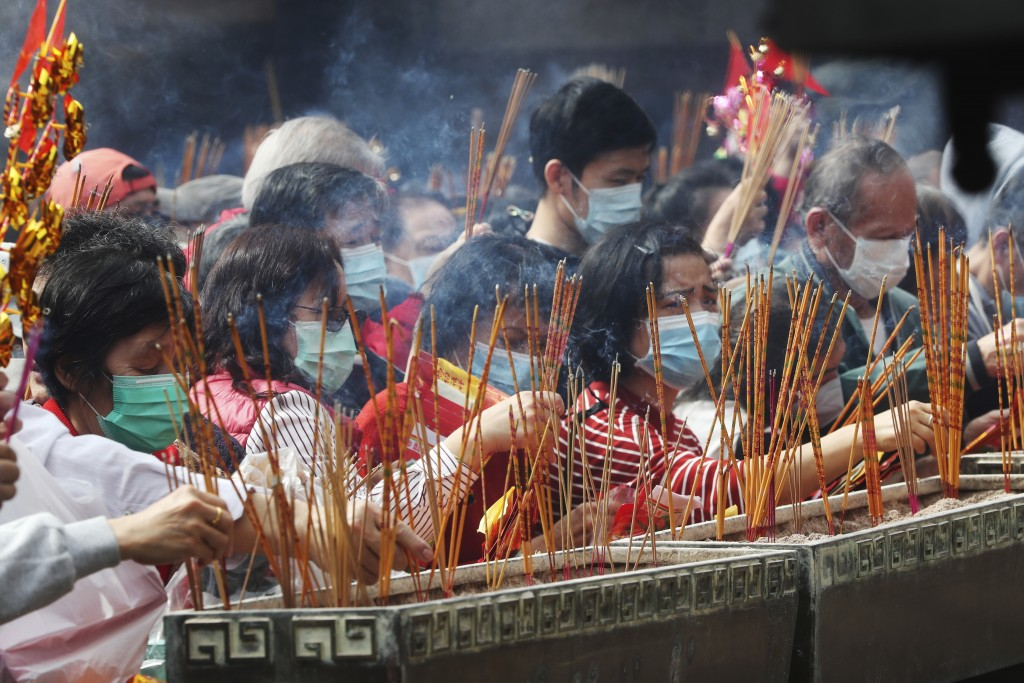 People burn joss sticks as they pray at the Wong Tai Sin Temple, in Hong Kong, Saturday, Jan. 25, 2020 to celebrate the Lunar New Year which marks the...