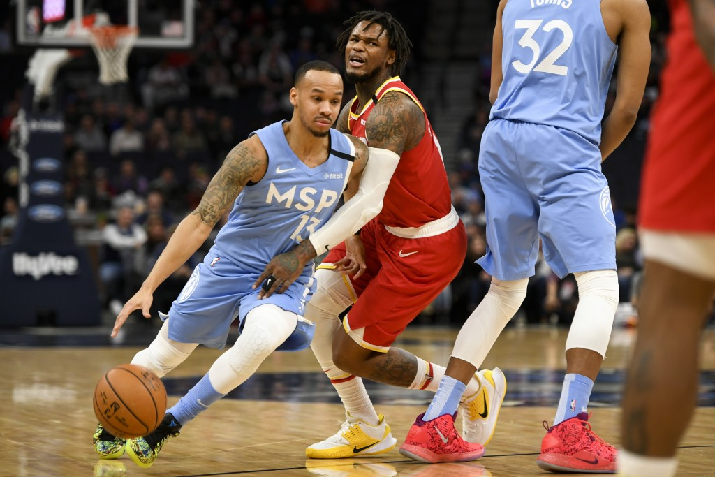 Minnesota Timberwolves guard Shabazz Napier, left, drives past Houston Rockets guard Ben McLemore during the first half of an NBA basketball game Frid...