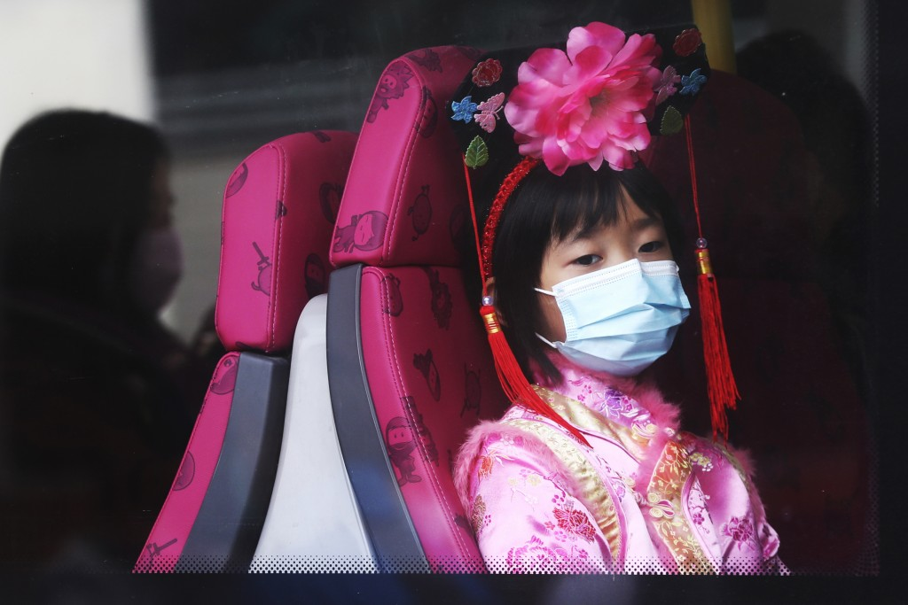 A girls wears a mask inside a bus in Hong Kong, Saturday, Jan. 25, 2020. China's most festive holiday began in the shadow of a worrying new virus ...