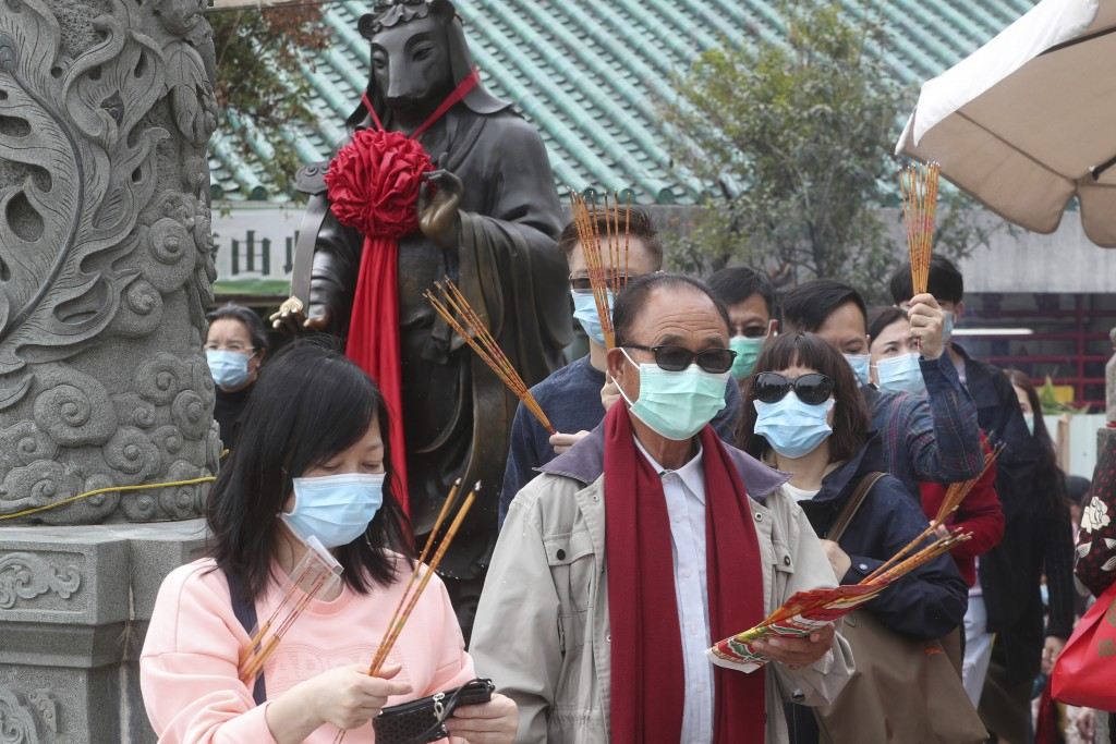 People wear masks as they pray at the Wong Tai Sin Temple, in Hong Kong, Saturday, Jan. 25, 2020 to celebrate the Lunar New Year which marks the Year ...