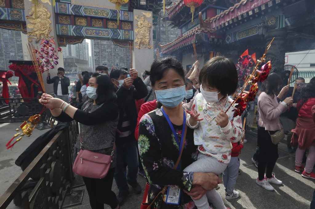 A women carries a girls as they pray at the Wong Tai Sin Temple, in Hong Kong, Saturday, Jan. 25, 2020 to celebrate the Lunar New Year which marks the...