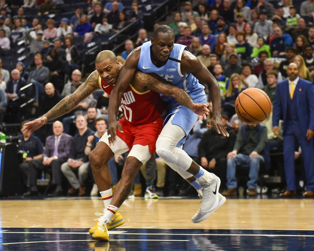 Minnesota Timberwolves center Gorgui Dieng, right, fouls Houston Rockets forward P.J. Tucker, left, as they battle for the ball during the first half ...