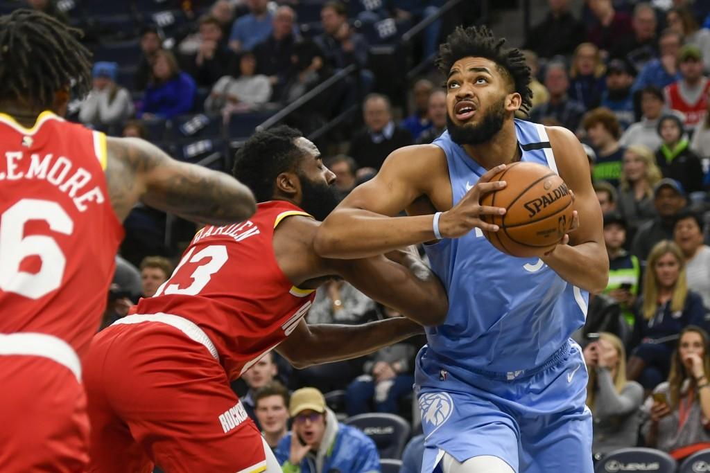 Minnesota Timberwolves center Karl-Anthony Towns, right, drives past Houston Rockets guard James Harden during the first half of an NBA basketball gam...