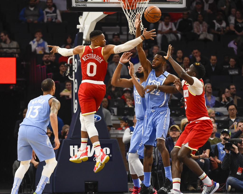 Houston Rockets guard Russell Westbrook (0) passes behind his back to center Clint Capela, right, as Minnesota Timberwolves center Karl-Anthony Towns ...