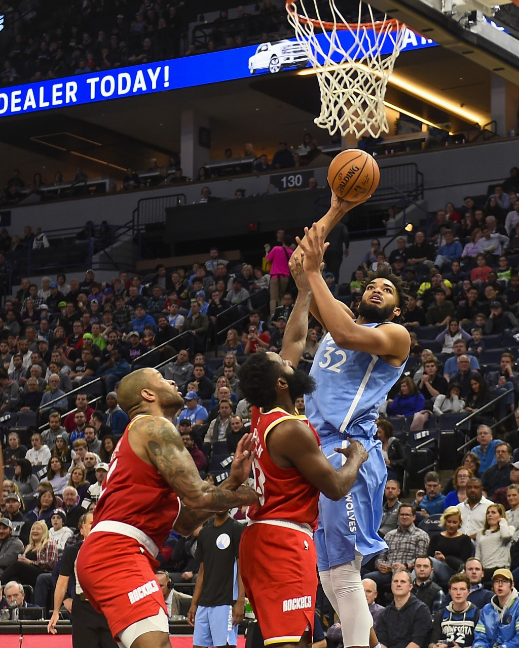 Minnesota Timberwolves center Karl-Anthony Towns (32) goes up to shoot as Houston Rockets guard James Harden, center, and forward P.J. Tucker look on ...