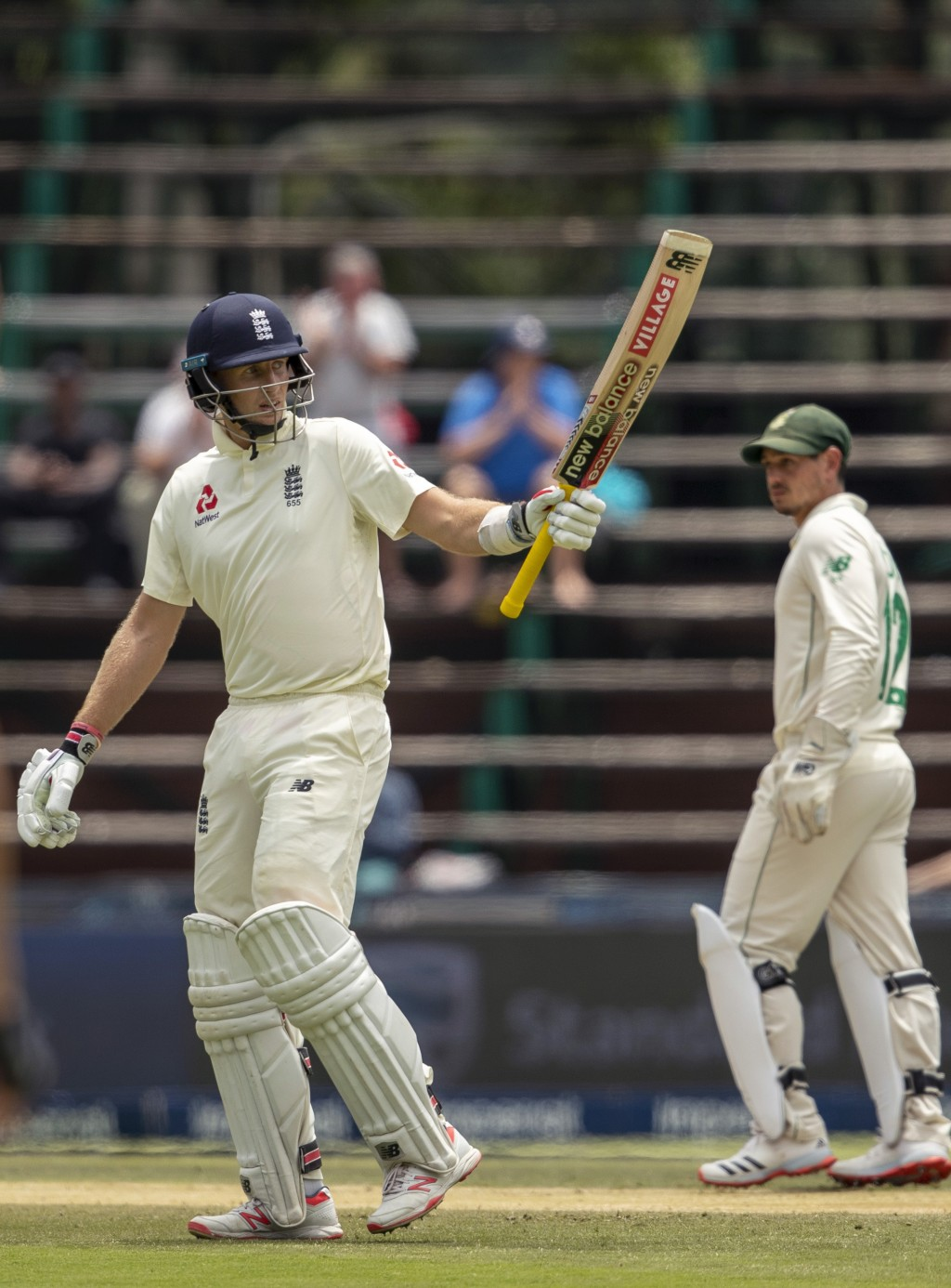 England's captain Joe Root raises his bat after reaching a half century on day two of the fourth cricket test match between South Africa and England a...