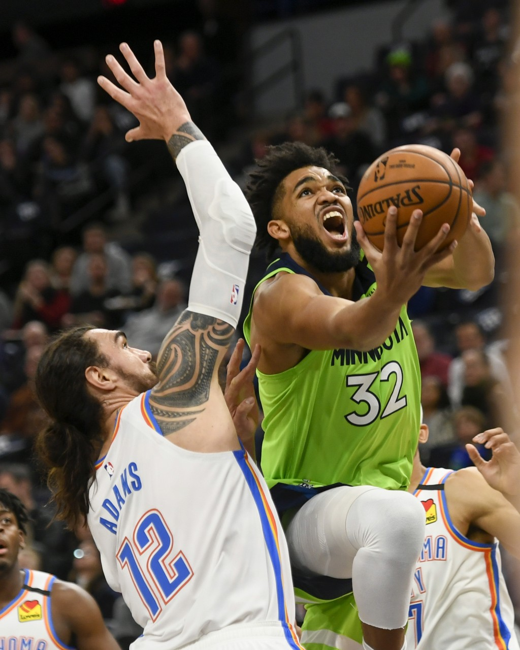 Minnesota Timberwolves center Karl-Anthony Towns(32) goes up to shoot past Oklahoma City Thunder center Steven Adams(12) during the first half of an...