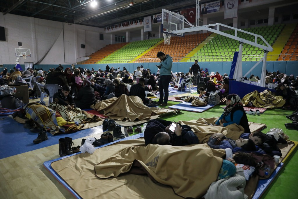 People gather inside a sports hall to spend the night following Friday's earthquake that destroyed their houses, in Elazig, eastern Turkey, late Satur...