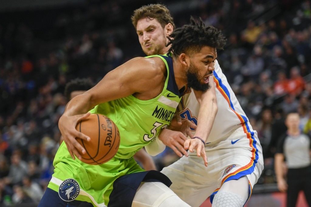 Minnesota Timberwolves center Karl-Anthony Towns collides with Oklahoma City Thunder forward Mike Muscala during the first half of an NBA basketball ...