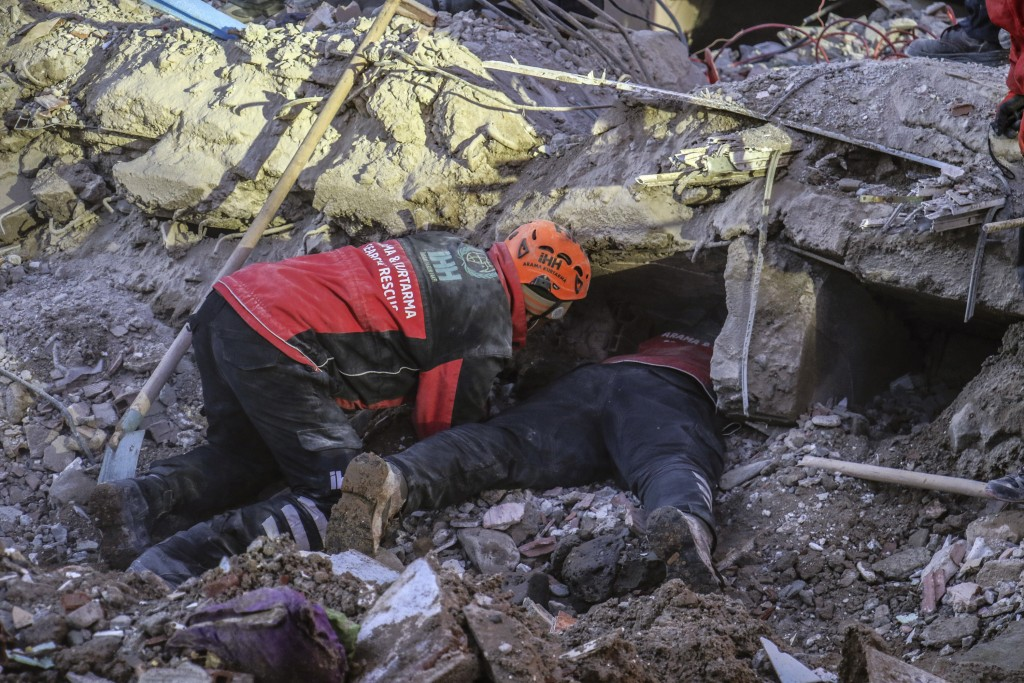 Rescue workers try to save people trapped under debris following a strong earthquake that destroyed several buildings on Friday, in Elazig, eastern Tu...