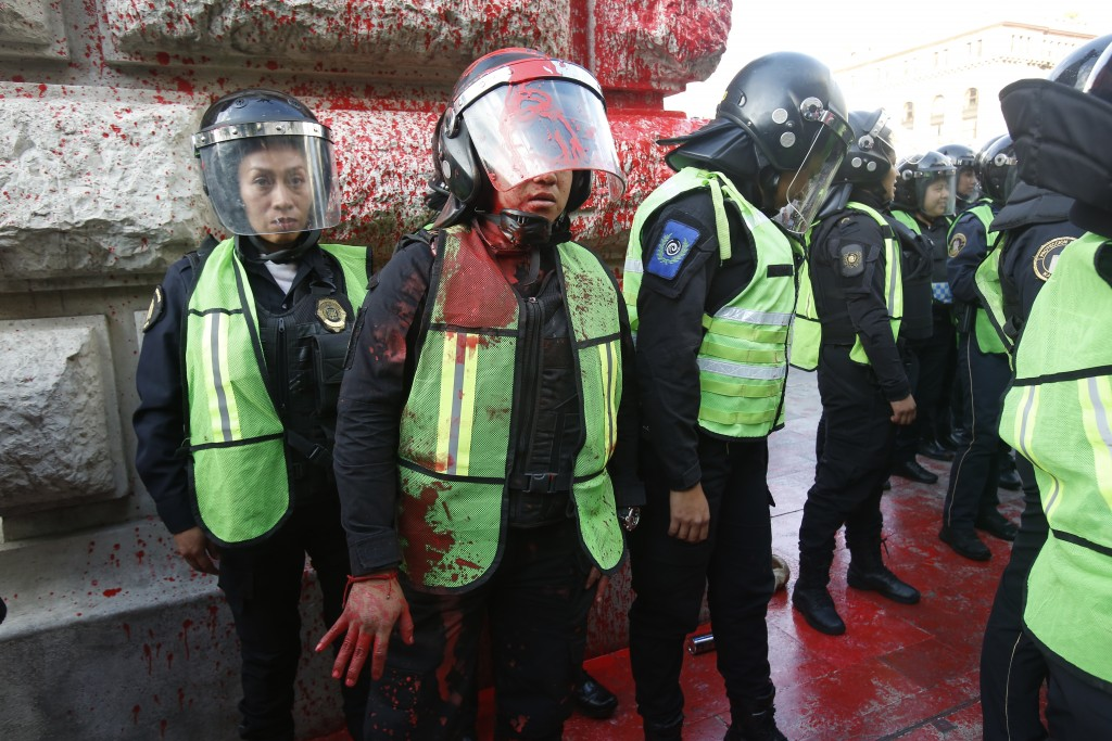 A female police officer covered in red paint stands by during a women's protest against the latest murder of two women, in Mexico City, Saturday, Jan....