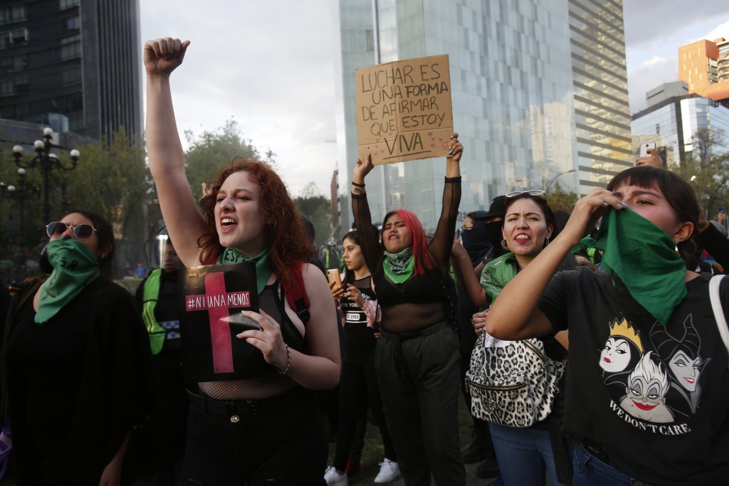 """Women, one holding a sing that reads in Spanish """"Fighting is way to reaffirm that I am alive,""""  protest against the latest murder of two women, in Mex..."""