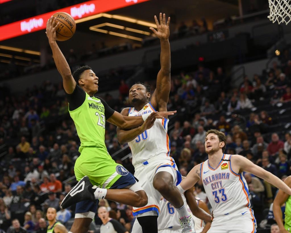 Oklahoma City Thunder guard Deonte Burton, center, blocks a shot by Minnesota Timberwolves guard Jarrett Culver, left, as Thunder forward Mike Muscala...