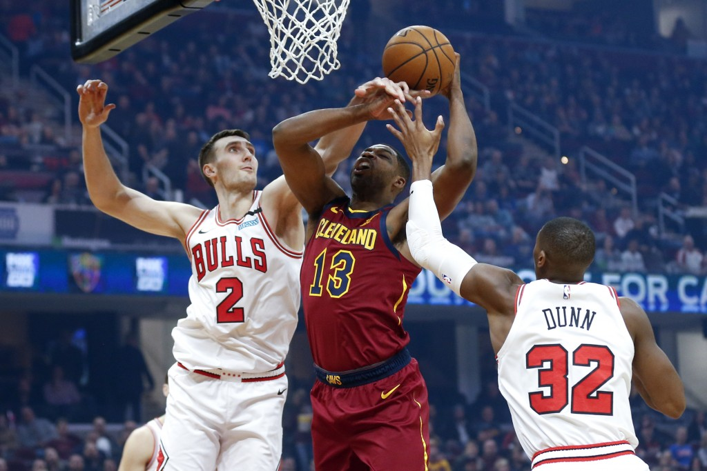 Cleveland Cavaliers' Tristan Thompson (13) grabs a rebound between Chicago Bulls' Luke Kornet (2) and Kris Dunn (32) in the first half of an NBA baske...