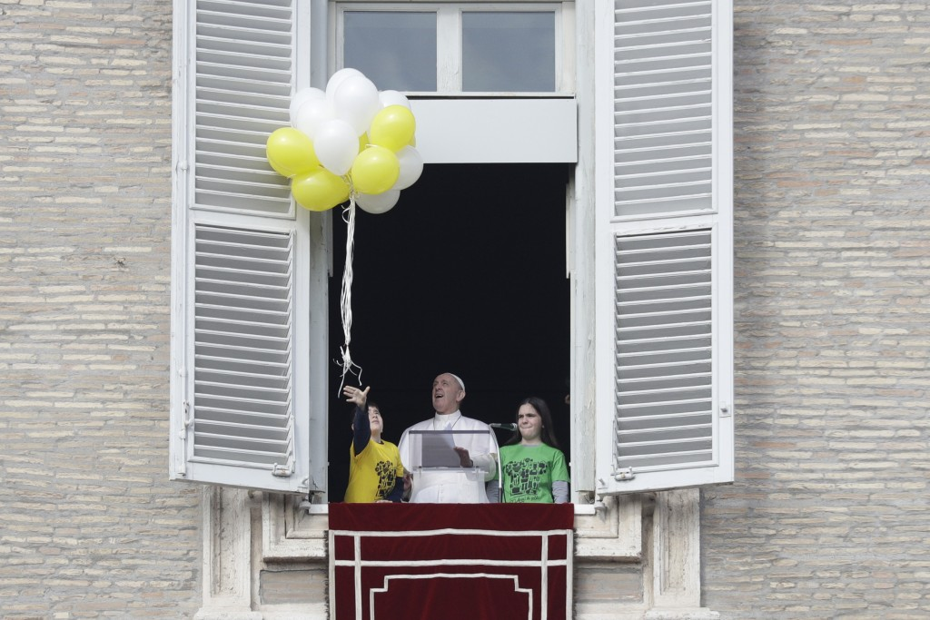 Pope Francis looks at balloons released by a child during the Angelus noon prayer at the Vatican, Sunday, Jan. 26, 2020. (AP Photo/Gregorio Borgia)