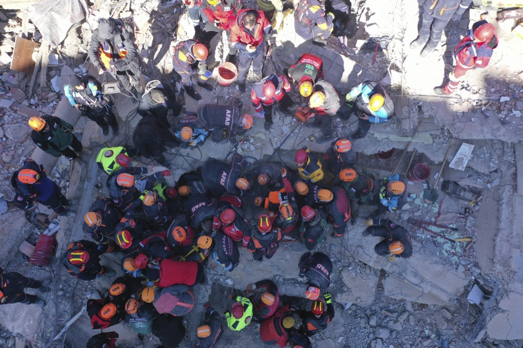 Rescuers work on searching for people buried under the rubble on a collapsed building, after an earthquake struck Elazig, eastern Turkey, Saturday, Ja...
