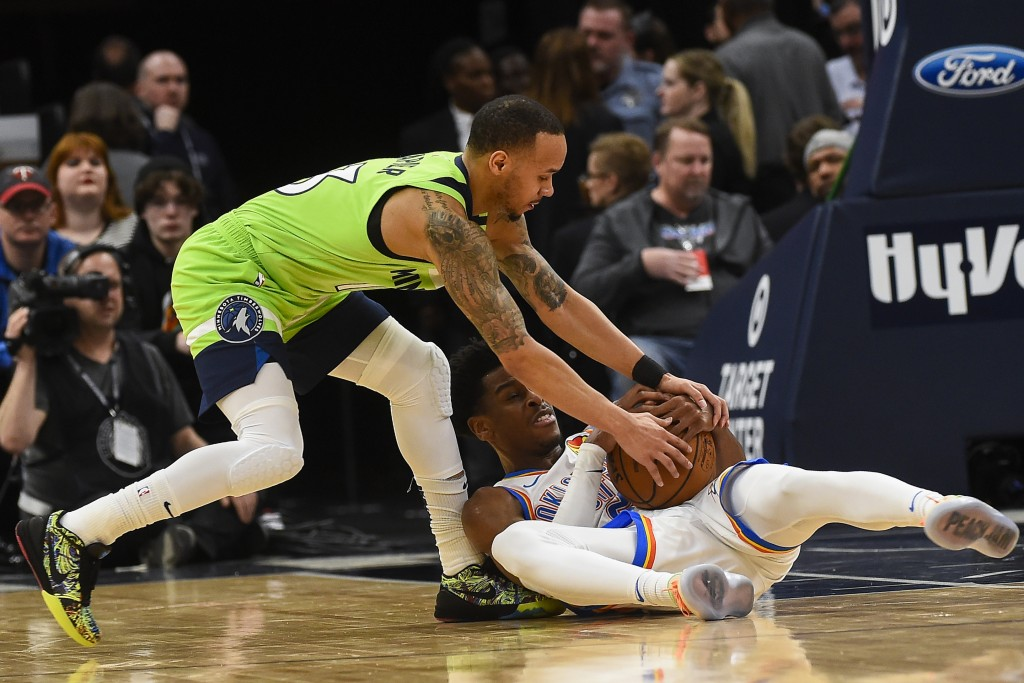 Minnesota Timberwolves guard Shabazz Napier, left, and Oklahoma City Thunder guard Shai Gilgeous-Alexanderfight for a loose ball resulting in a jump ...