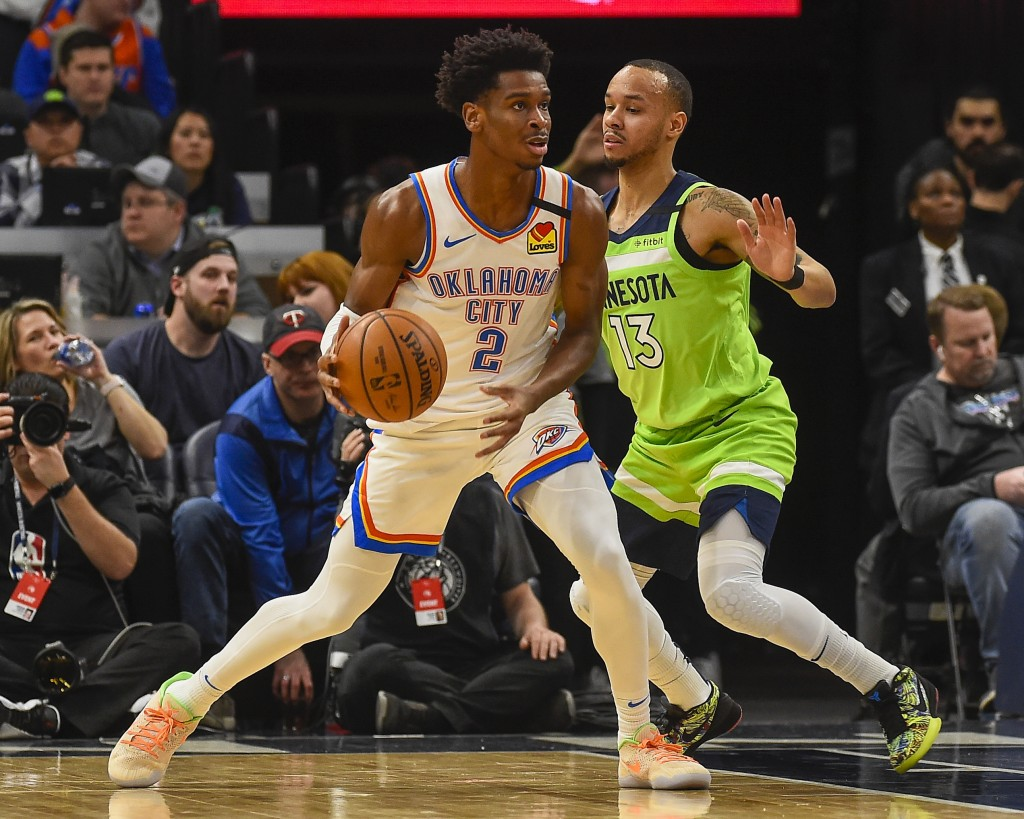 Oklahoma City Thunder guard Shai Gilgeous-Alexander(2) looks to pass the ball while defended by Minnesota Timberwolves guard Shabazz Napier(13) duri...