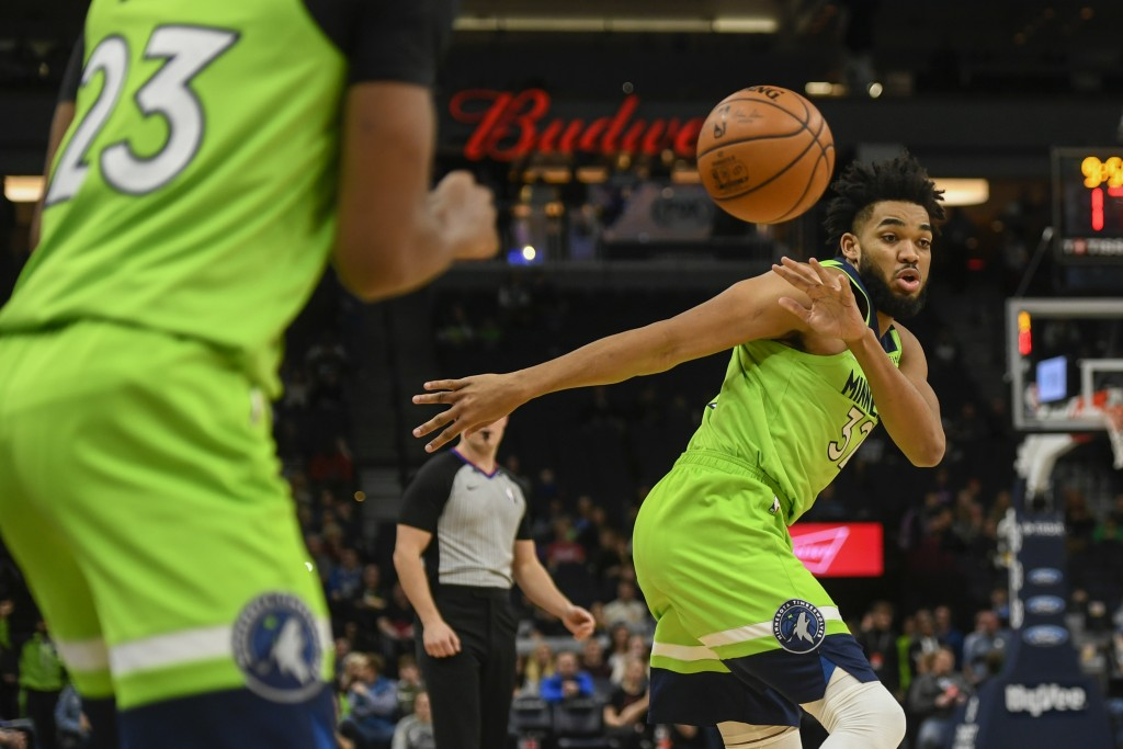 Minnesota Timberwolves center Karl-Anthony Towns, right, passes the ball to Minnesota Timberwolves guard Jarrett Culver during the first half of an NB...
