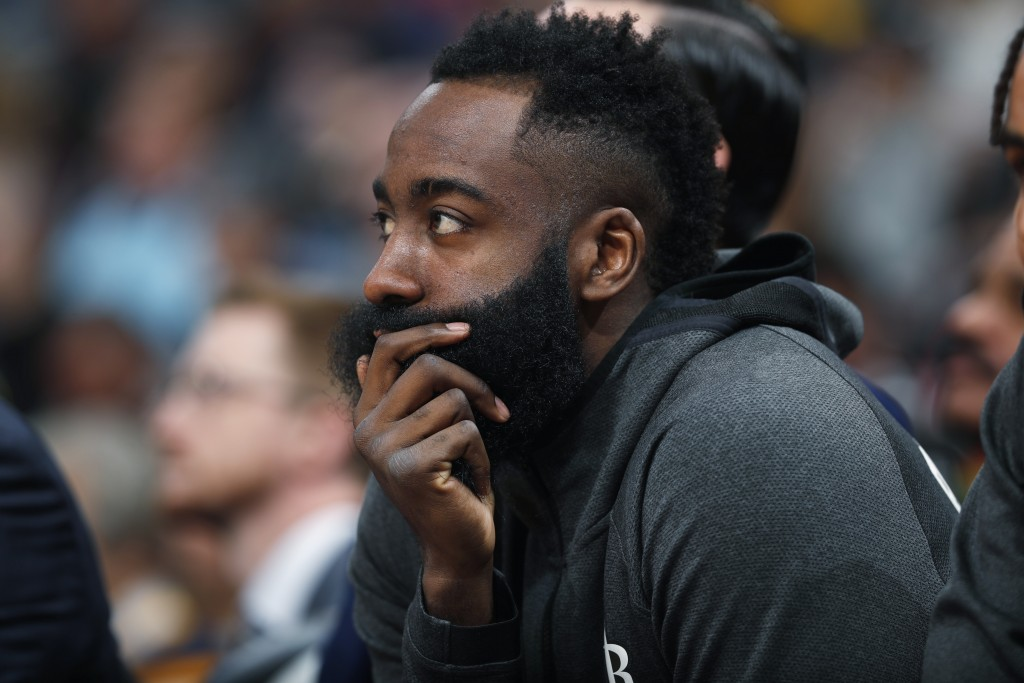 Houston Rockets guard James Harden looks on from the bench in the first half of an NBA basketball game against the Denver Nuggets, Sunday, Jan. 26, 20...