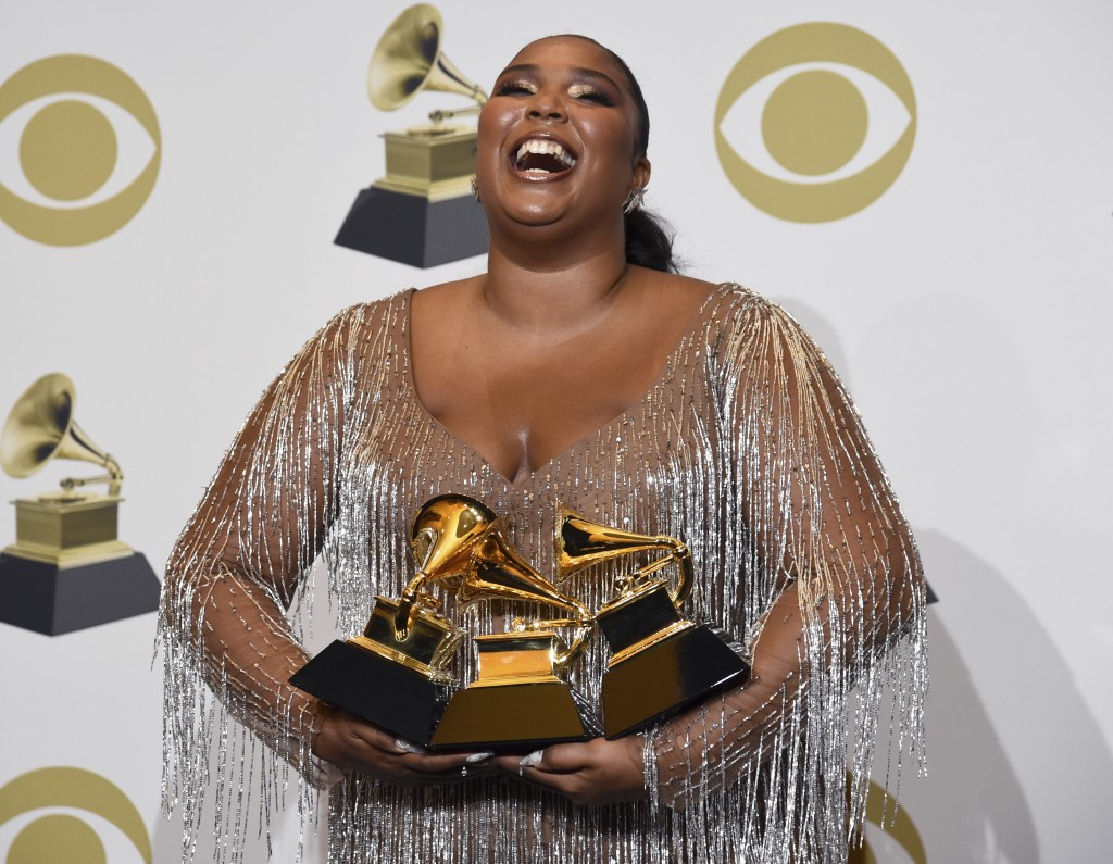 """Lizzo poses in the press room with the awards for best pop solo performance for """"Truth Hurts"""", best urban contemporary album for """"Cuz I Love You"""" and ..."""