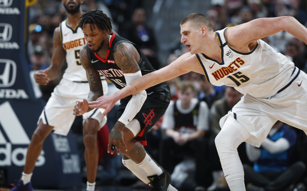 Houston Rockets guard Ben McLemore, font left, pursues the ball with Denver Nuggets center Nikola Jokic in the first half of an NBA basketball game Su...