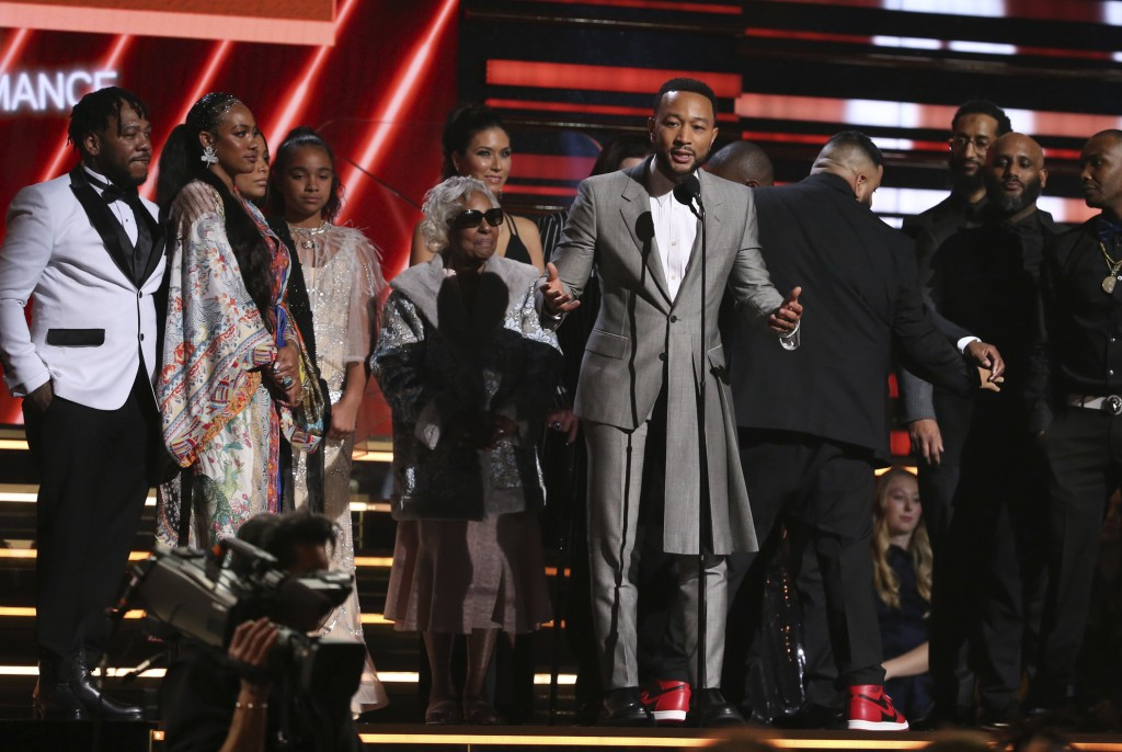 John Legend, center, DJ Khaled and members of Nipsey Hussle's family accept the award for best rap/sung performance at the 62nd annual Grammy Awards o...
