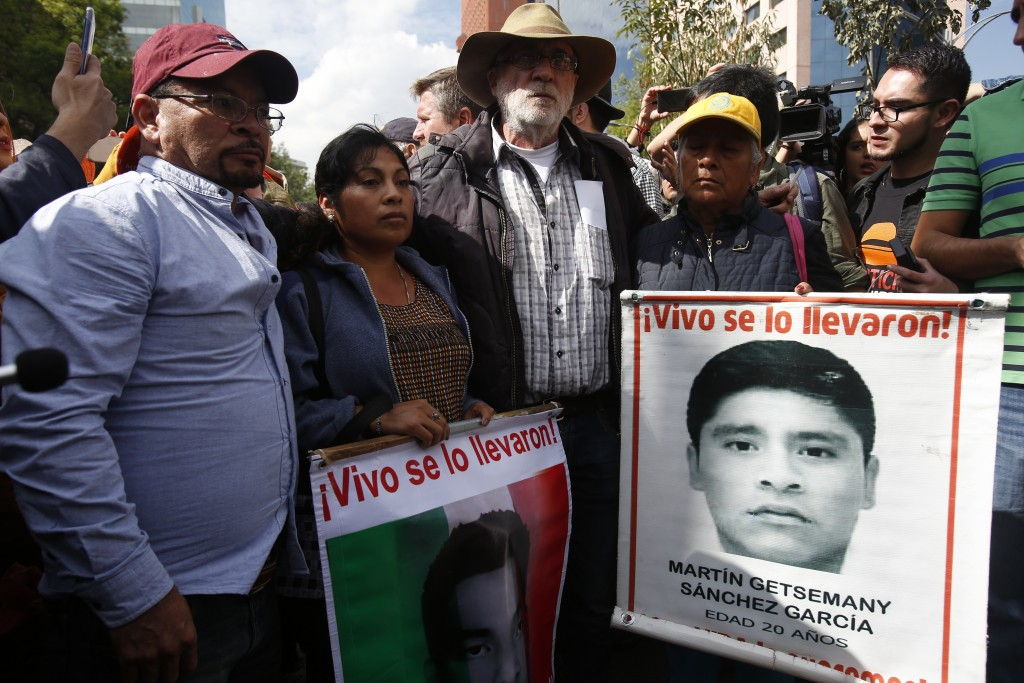 Poet and activist Javier Sicilia, center, stands with the relatives of 43 students that went missing in Sept. 2014, during a march against violence ca...