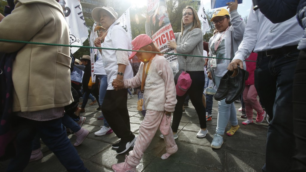 People march with members of the LeBaron family and activist and poet Javier Sicilia, with one shoe off in memory of a LeBaron child that walked baref...