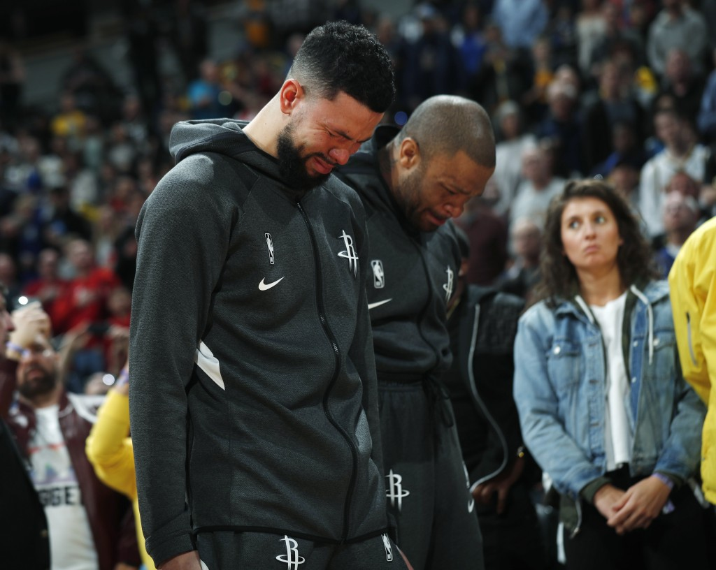 Houston Rockets guard Austin Rivers and forward P.J. Tucker react during a tribute to NBA star Kobe Bryant before an NBA basketball game against the D...