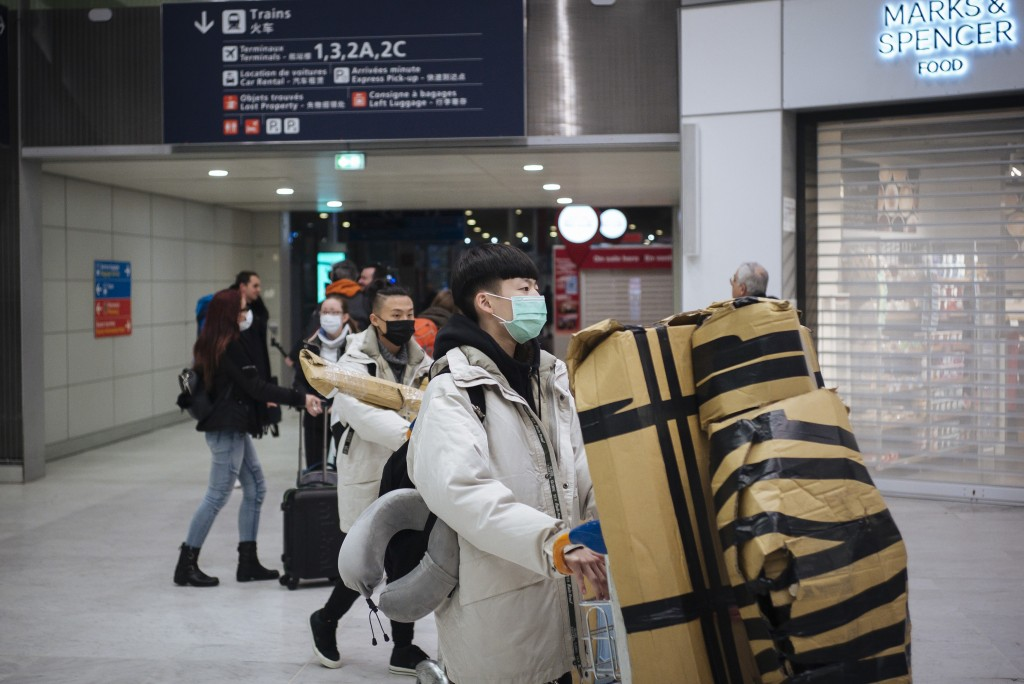 Travelers from Beijing , wearing masks, arrive at Charles de Gaulle airport, north of Paris, early Monday, Jan. 27, 2020. France's government announce...