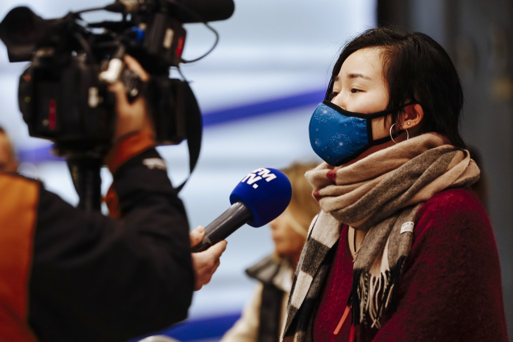 A traveler from Beijing speaks to a french TV named BFM TV as she arrives at Charles de Gaulle airport, north of Paris, early Monday, Jan. 27, 2020. F...