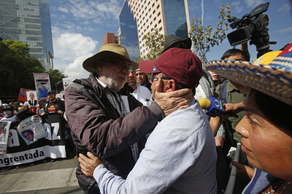 Activist and poet  Javier Sicilia embraces a father of one of the 43 students that went missing in Sept. 2014, during a march against violence called ...