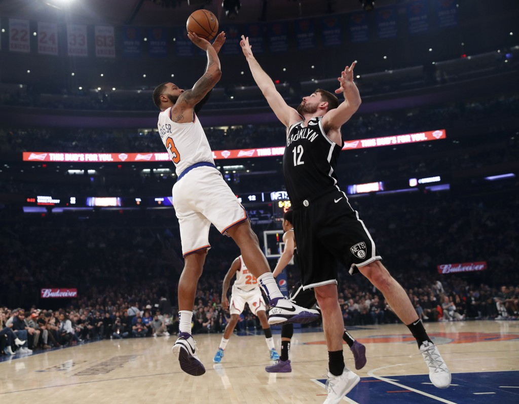 New York Knicks forward Marcus Morris Sr. (13) shoots with Brooklyn Nets forward Joe Harris (12) defending during the first half of an NBA basketball ...