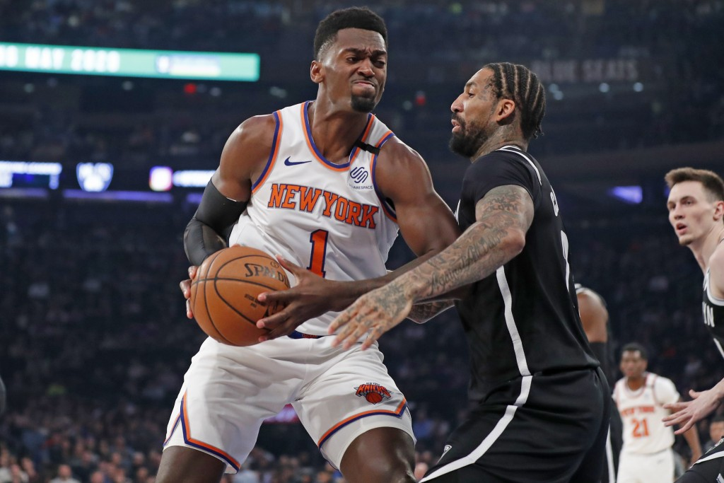 Brooklyn Nets forward Wilson Chandler (21) defends New York Knicks forward Bobby Portis (1) as Portis rives to the basket during the first half of an ...
