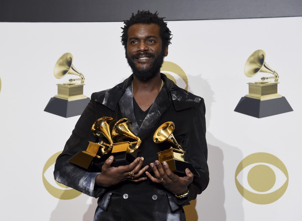 """Gary Clark Jr. poses in the press room with the awards for best rock song, best rock performance and best contemporary blues album for """"This Land"""", at..."""