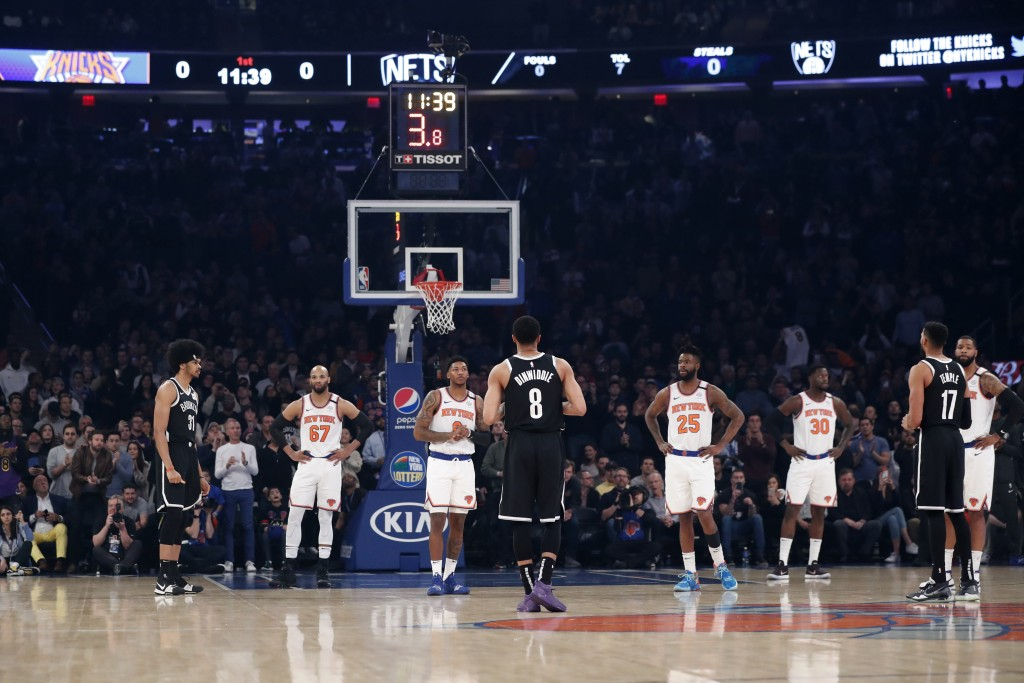 New York Knicks and Brooklyn Nets players stand on the court allowing the 24 second clock to wind down in a tribute to retired Los Angeles Lakers star...