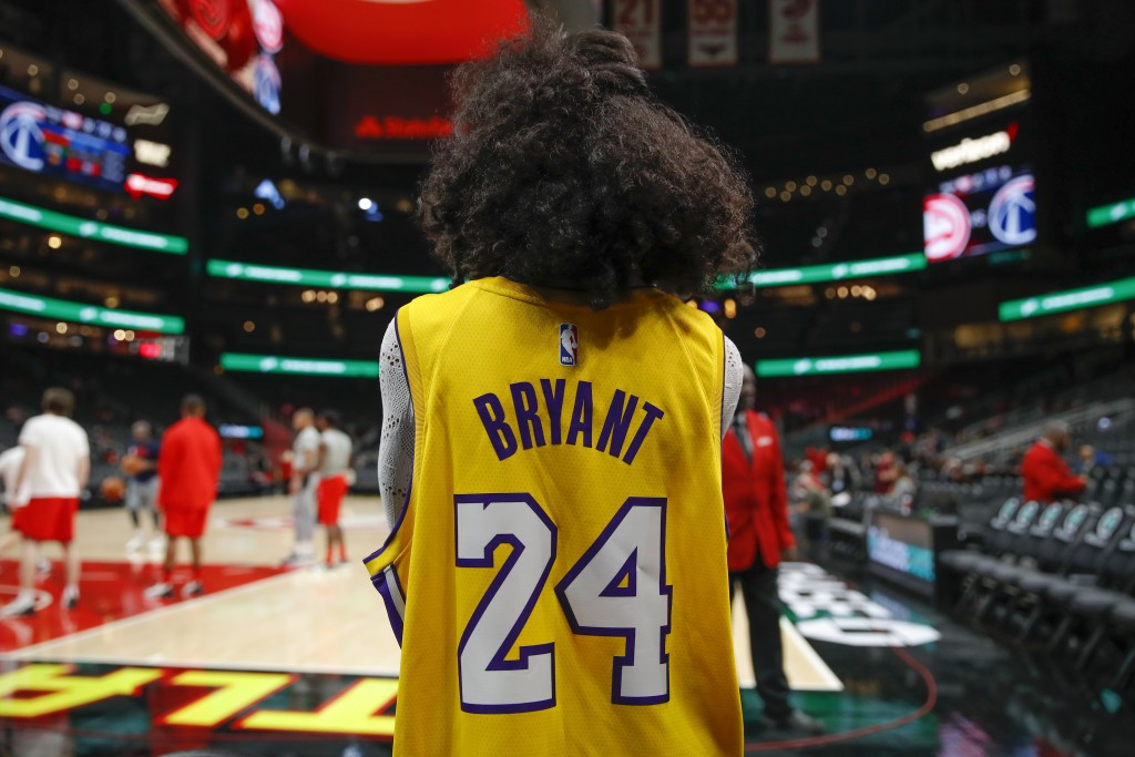 A fan watches warmups while wearing a Kobe Bryant jersey after news reports of his death in a helicopter crash prior to an NBA basketball game between...