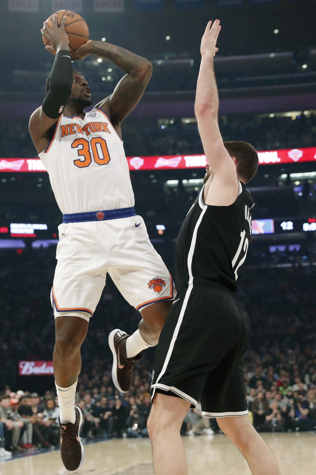 New York Knicks forward Julius Randle (30) attempts a three-point shot over Brooklyn Nets forward Joe Harris (12) during the first half of an NBA bask...