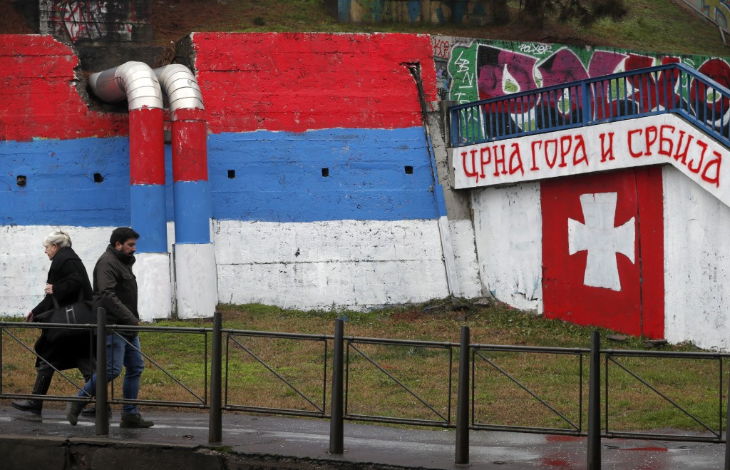 """People walk by graffiti showing a Serbian flag, left, and text reading """"Montenegro and Serbia'' in Belgrade, Serbia, Monday, Jan. 27, 2020. (AP Photo/..."""