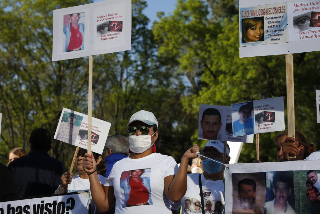 """People hold signs of their dead and missing relatives during a march against violence called """"Walk for Peace,"""" in Mexico City, Sunday, Jan. 26, 2020. ..."""