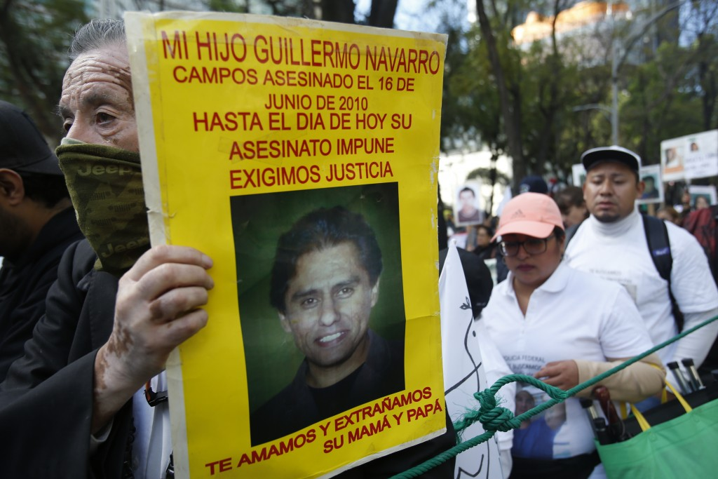 """A demonstrator carries a poster with the photo of his murdered son during a march against violence called """"Walk for Peace,"""" in Mexico City, Sunday, Ja..."""