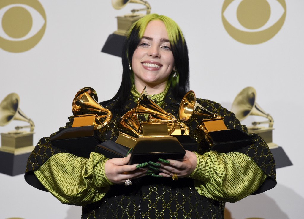 """Billie Eilish poses in the press room with the awards for best album and best pop vocal album for """"We All Fall Asleep, Where Do We Go?"""", best song and..."""